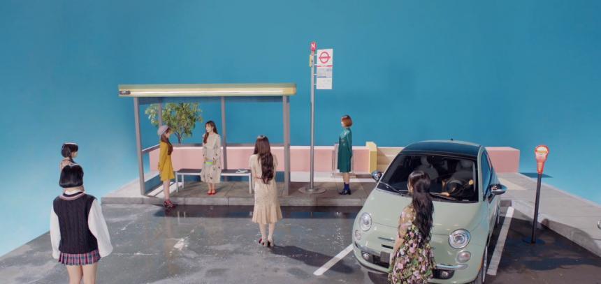 '비밀정원' 뮤직비디오 마지막 장면. 정류장에 서 있는 아린 중심으로 오마이걸 멤버들이 모두 모여 있다