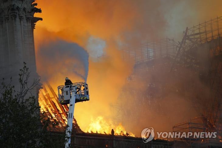 프랑스 파리 노트르담 대성당에서 지난 15일(현지시간) 대형 화재가 발생하자 소방관이 출동해 진화작업을 하는 모습. [AP=연합뉴스]