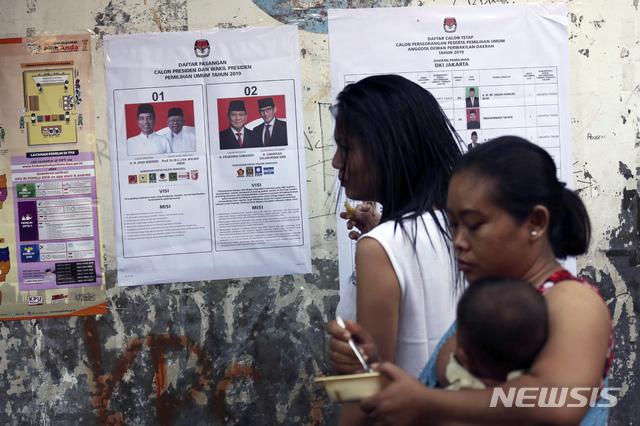 인도네시아에서 17일(현지시간) 대통령과 국회의원을 뽑는 선거의 투표가 시작돼 자카르타의 한 투표소에서 유권자들이 대통령 후보 벽보를 살펴보고 있다. / 뉴시스