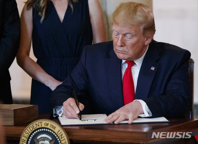 도널드 트럼프 미국 대통령이 24일(현지시간) 백악관 집무실에서 병원이 일반 검사와 시술의 실제 비용을 사전 공개하라는 행정명령에 서명하고 있다. 2019.06.25. / 워싱턴=AP/뉴시스
