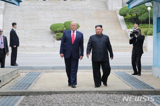 도널드 트럼프 미국 대통령이 30일 판문점 공동경비구역(JSA) 군사분계선 북측 지역에서 김정은 북한 국무위원장과 만나 군사분계선을 넘어 오고 있다. 2019.06.30. / 뉴시스