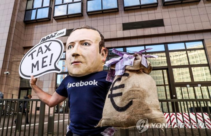 프랑스, IT 공룡들에 디지털세 부과 추진. 마크 저커버그 페이스북 최고경영자(CEO) 탈을 쓴 한 활동가가 '내게 세금을 걷어라'고 쓰인 표지를 들고 있다. [EPA=연합뉴스 자료사진]