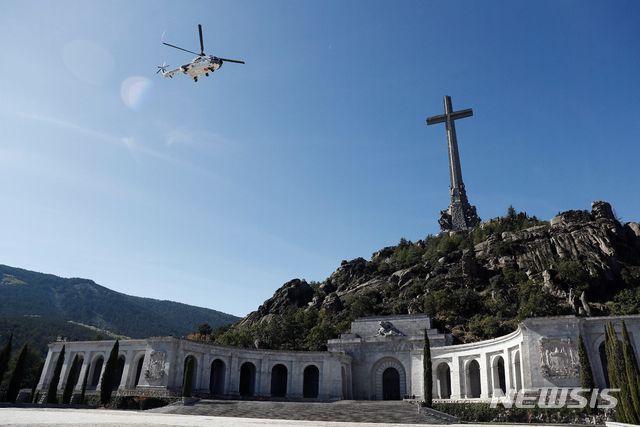 전몰용사 계곡의 국립묘지에서 다시 꺼내어진 프랑코의 관이 헬기로 이송되고 있다. 바실리카 양식의 대회당 전면 한가운데에 프랑코의 묘가 있었다. 3만 명이 매장되어 있으며 계곡 산 뒤에 세워진 십자가는 150m 높이의 장관을 자랑한다. AP/뉴시스
