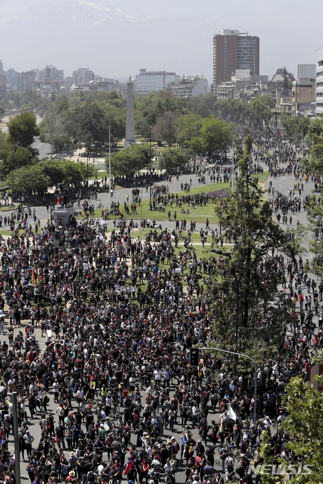 21일(현지시간) 칠레 수도 산티아고에 학생과 노동조합 조합원들이 반정부 시위를 위해 모여들고 있다. 지하철 요금 인상으로 촉발된 반정부 시위가 산티아고를 비롯, 칠레 전역에서 이어지는 가운데 지금까지 20명이 사망한 것으로 알려졌다. 2019.10.22. 【산티아고=AP/뉴시스】