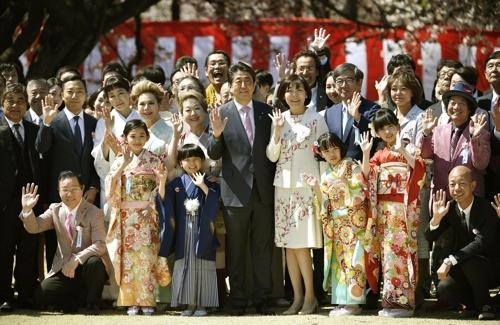아베 신조 총리가 지난 4월 13일 도쿄 도심 공원인 '신주쿠 교엔'에서 열린 '사쿠라 나들이 모임'(桜を見る会) 행사에서 참석자들과 기념사진을 찍고 있다. [교도=연합뉴스 자료사진]