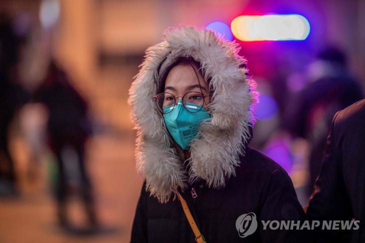 베이징 기차역 앞의 마스크 쓴 여성. 중국에서 신종 코로나바이러스가 일으키는 '우한 폐렴'의 사망자가 급증하는 가운데 마스크를 착용한 한 여성이 22일 베이징 기차역 앞 거리를 걸어가고 있다. / 연합뉴스