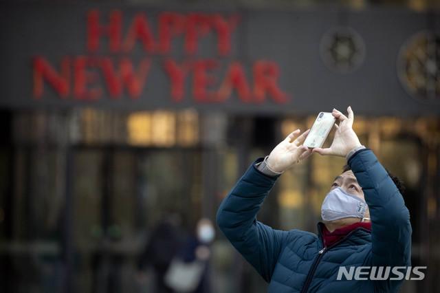 22일(현지시간) 중국 전역에 신종 코로나바이러스가 확산한 가운데 베이징에서 한 남성이 마스크를 쓴 채 사진을 찍고 있다. 2020.01.24. / 뉴시스