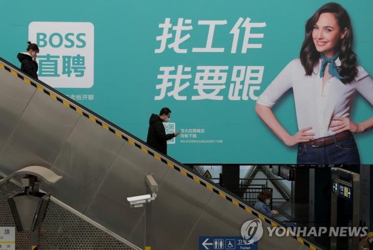 많은 기업이 업무를 재개한 10일 베이징에서 사람들이 마스크를 쓴 채 구직 플랫폼 광고 앞의 에스컬레이터에 서 있다. [로이터=연합뉴스]