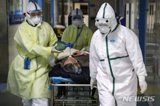 중국 후베이성 우한의 한 병원에서 6일 보호복을 입은 의료진이 코로나 19 환자를 격리병동으로 옮기고 있다. 2020.02.13 / 뉴시스