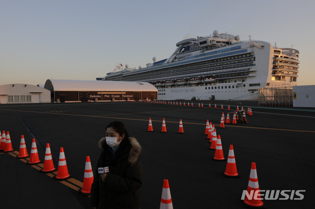 지난 13일 일본 도쿄 인근 요코하마항에 정박한 유람선 다이아몬드 프린세스 주변에서 CCTV 리포터가 방송하고 있다. 이날 유람선 내 신종 코로나바이러스 감염증(코로나19) 감염자가 218명으로 불어난 가운데 세계보건기구(WHO)는 해상에 강제 격리된 채 정박해 있는 다이아몬드 프린세스호에 대해 자유로운 입항 허가와 적절한 조처를 촉구했다. 2020.02.15 / 뉴시스
