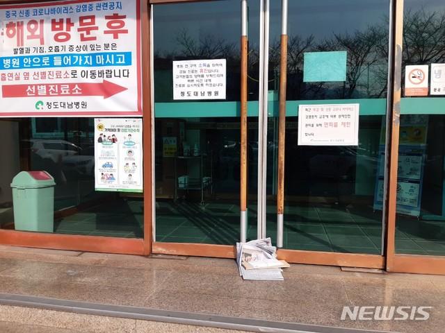 21일 오전 청도 대남병원의 출입문이 봉쇄된 모습. 이날 배달된 신문이 방치돼 있다. / 뉴시스