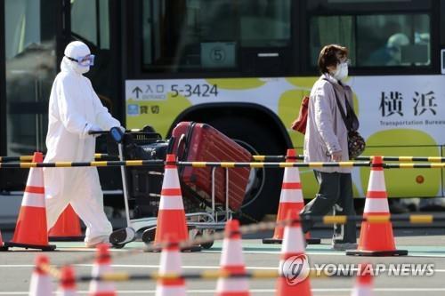 21일 방호복을 착용한 당국자가 일본 요코하마(橫浜)항에 정박 중인 크루즈선 다이아몬드 프린세스에서 내린 승객의 짐을 운반하고 있다. / 연합뉴스