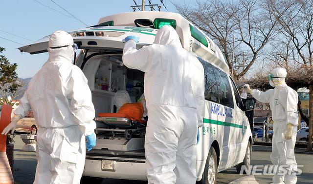 신종 코로나바이러스 감염증(코로나19)으로 국내 첫 사망자가 발생한 곳으로 알려진 21일 오후 경북 청도군 대남병원에서 질병관리본부 관계자들이 코로나19 의심 환자를 이송하고 있다. / 뉴시스