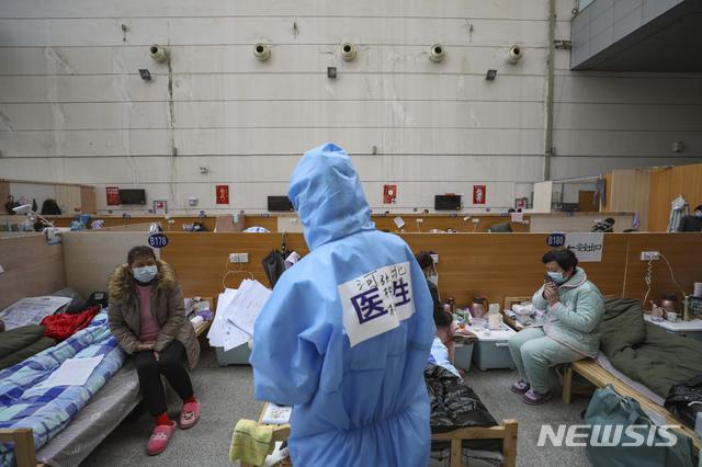 21일(현지시간) 중국 후베이성 우한의 타즈후 체육센터에 마련된 임시 병원에서 한 의료 종사자가 신종 코로나바이러스 감염증(코로나19) 환자들을 진료하고 있다. 중국 국가위생건강위원회는 22일 오전 0시 기준 코로나19 사망자가 총 2345명, 확진자는 총 7만6288명이라고 공식 발표했다. 2020.02.22. / 뉴시스