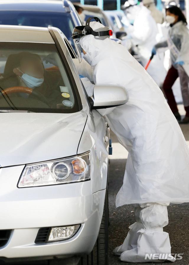 시민이 27일 경기 고양시 주교동 내 공용주차장에 마련된 차에 탄 채로 검사받는 '드라이브 스루(Drive Thry)' 식 선별진료소인 '고양 안심 카 선별진료소'에서 신종 코로나바이러스 감염증(코로나19) 검사를 받고 있다. 2020.02.27. / 뉴시스