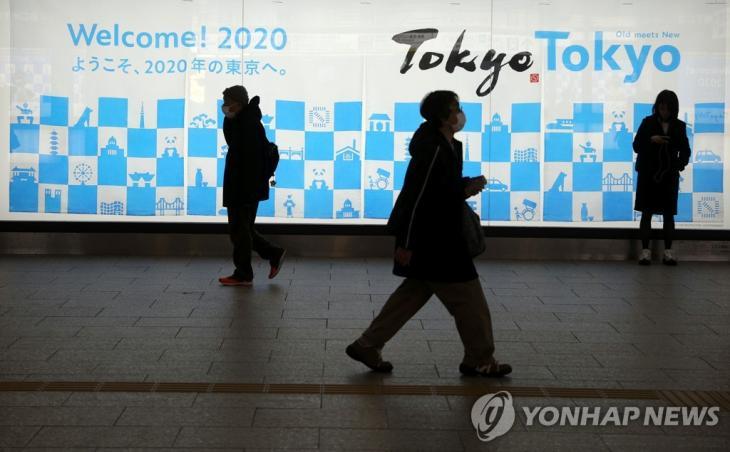 일본 도쿄 신주쿠역 근처의 도쿄올림픽 광고 표지판 앞을 걷는 사람들의 모습. [로이터=연합뉴스]