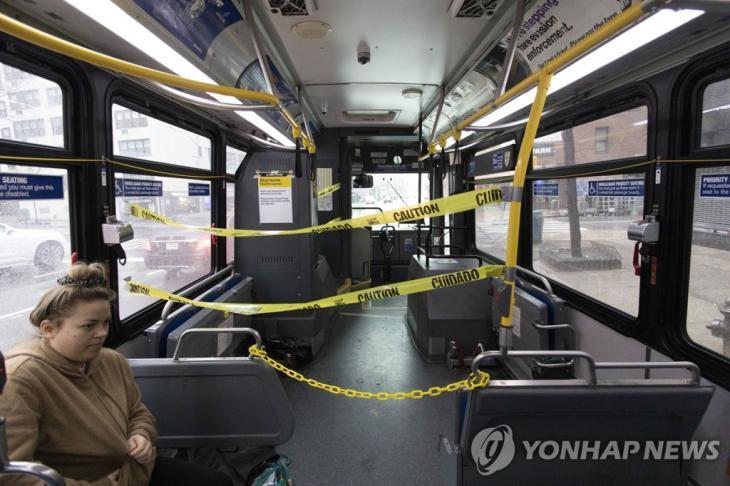 '코로나19 거리두기' 뉴욕 버스 안에 차단선 설치. 신종 코로나바이러스 감염증(코로나19) 예방을 위해 운전석 주변에 차단선이 설치된 미국 뉴욕 시내버스 안에 23일(현지시간) 한 여성이 탑승해 있다. / 연합뉴스