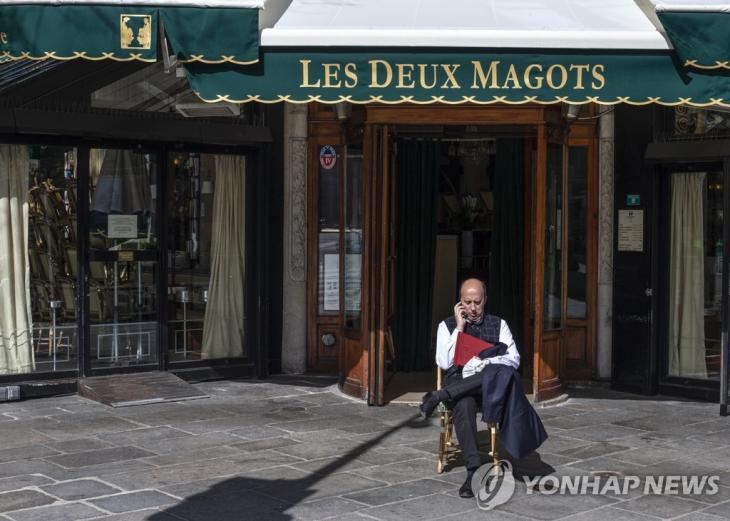 15일(현지시간) 신종 코로나바이러스 감염증(코로나19) 여파로 문을 닫은 프랑스 파리의 대표적 카페 '레 두 마고'(Les Deux Magots) 앞에 한 남성이 앉아 있다. 에두아르 필리프 프랑스 총리는 이날 코로나19 확산 방지를 위해 전국의 음식점과 카페 등 비필수 상점들을 15일부터 당분간 폐쇄한다고 발표했다. / 연합뉴스