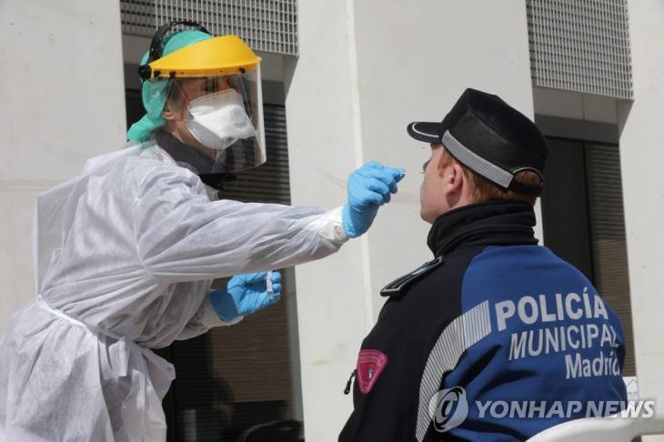 지난 25일 스페인 마드리드에서 한 경찰관이 코로나19 검사를 받는 모습. [마드리드시 제공·EPA=연합뉴스. 재판매 및 DB 금지]