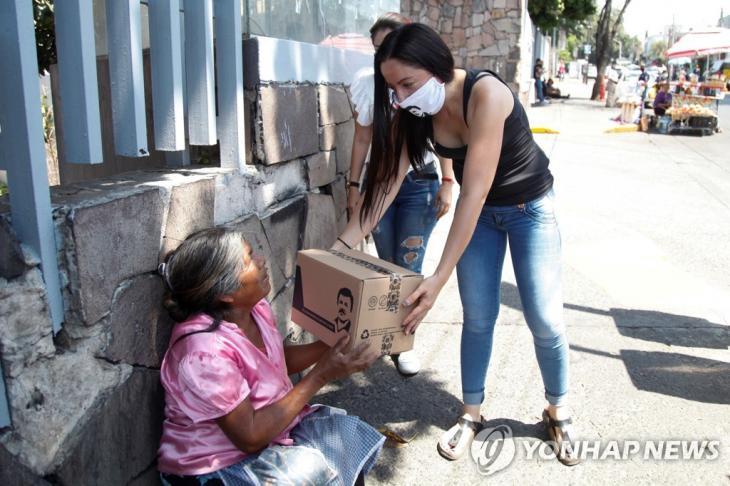 멕시코 과달라하라에서 마약왕 구스만의 얼굴이 그려진 구호품을 배포하는 모습 [EPA=연합뉴스]