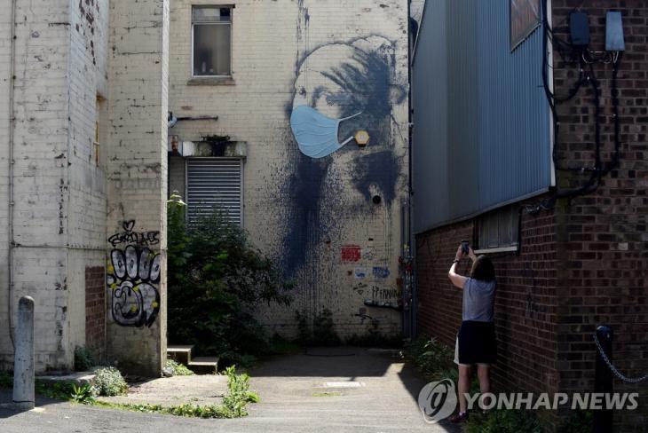 마스크가 새로 덧씌워진 뱅크시의 벽화 '피어싱을 한 소녀' [로이터=연합뉴스]