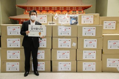 """감사 뜻 나타내는 일본 나라시장. 일본 나라시청에서 나카가와 겐 나라시장이 경북 경주시가 보낸 방역물품 앞에서 """"감사합니다""""란 팻말을 들고 서 있다. 2020.5.21 [경주시 제공]"""